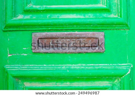 A letter box in a green old wooden door - stock photo