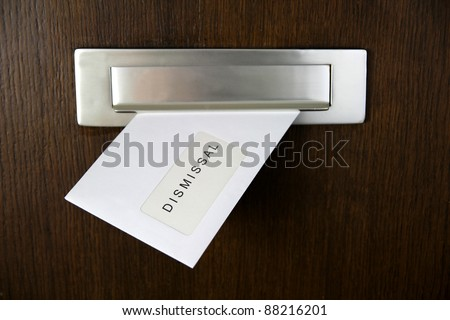 A letter in a letterbox of a door, written DISMISSAL - stock photo