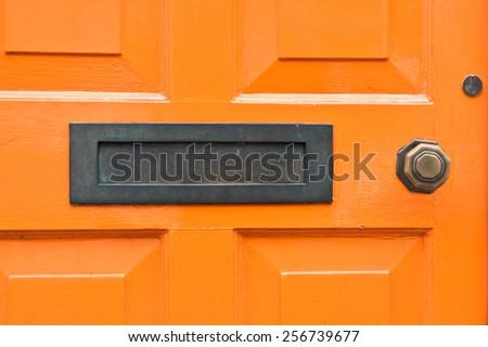 A letterbox in an orange wooden door - stock photo