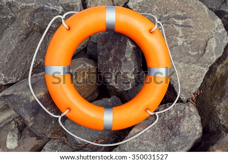 A life buoy on stones background - stock photo