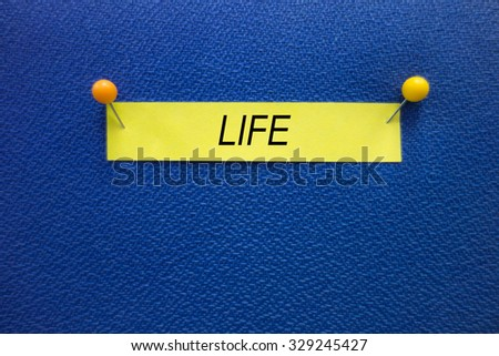 A LIFE wording on the yellow stick note pinned on the blue board, information concept. - stock photo