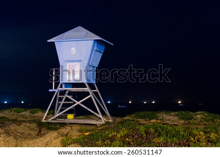 A lifeguard station on the beach at night with oil rigs behind - stock photo
