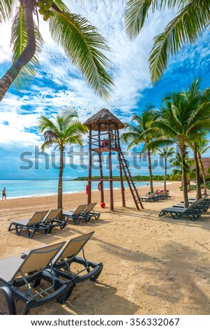 A lifeguard surveillance tower at the caribbean, tropical beach with palm trees and some lounges. Vertical. - stock photo