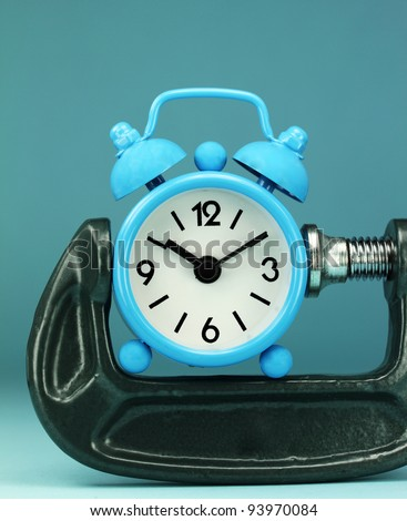 A light blue alarm clock placed in a Grey clamp against a pastel purple background, asking the question do you manage your time effectively. - stock photo