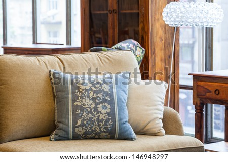 A light brown sofa with a cream and a blue pillow with flowers - stock photo