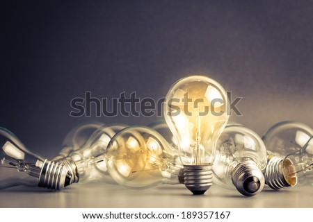 A light bulb that stable and glowing among the others - stock photo
