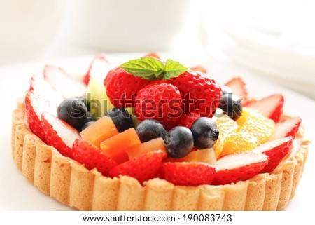 A light colored cake is full of fresh fruit. - stock photo