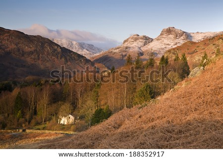 A light dusting of snow lies on top of the Langdale Pikes bathed in a warm winter sunrise in the English Lake District. - stock photo
