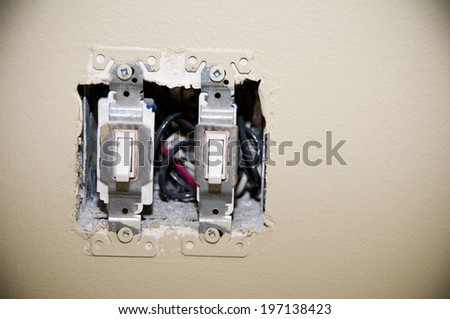 A light switch missing the cover plate on a wall. - stock photo