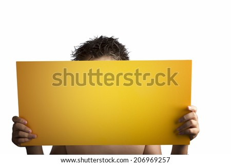 A light yellow orange plywood square blank signboard supported by young hands on light background. Face is covered and the contents of the sign are the main focus - stock photo