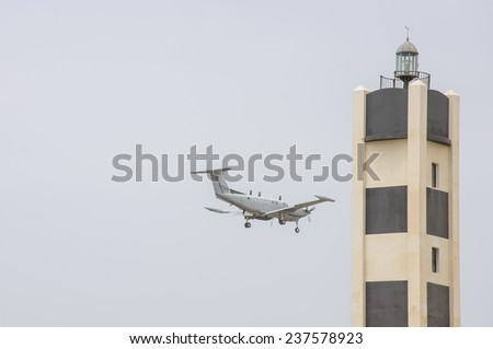 A lighthouse and Small private jet landing or taking off with background of grey sky - stock photo