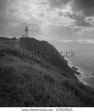 A lighthouse stands on top of a high rocky cliff to warn passing ships of danger. - stock photo