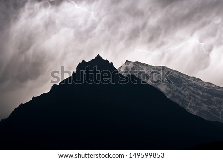 A lighting striking above two high mountain peaks. - stock photo