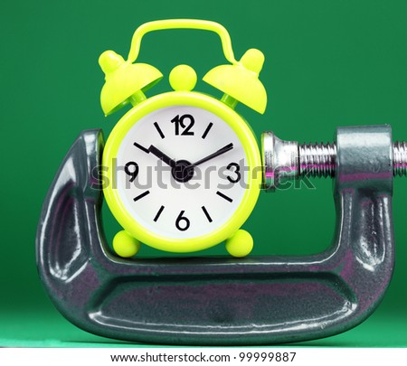 A lime green alarm clock placed in a Grey clamp against a light pastel blue background, asking the question do you manage your time effectively. - stock photo