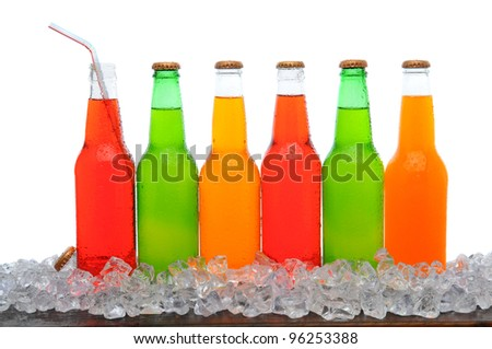 A line of assorted soda bottles standing in a field of ice cubes on a wooden table. Horizontal format with a white background. - stock photo