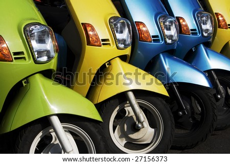 A line of mopeds/scooters, gleaming and shiny.  They look as if they are ready to go. - stock photo