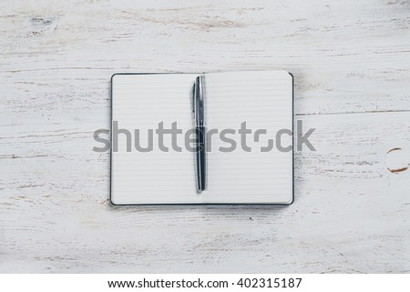 A lined notebook for notes is placed on a table in white lacquered wood, with a pen to write, the pages are blank, no writing and no drawings. Top view - stock photo