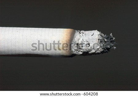 A lit cigarette isolated on black - stock photo