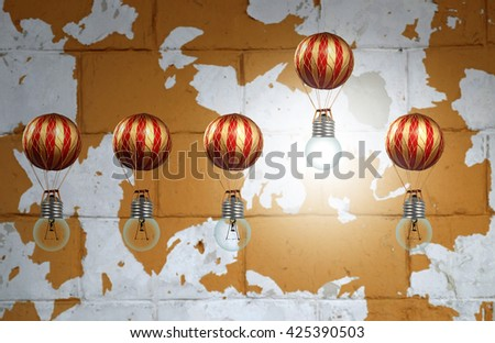A lit lightbulb powering a balloon above the others against a grungy urban environment for the concept of rising above the rest with a bright idea. - stock photo