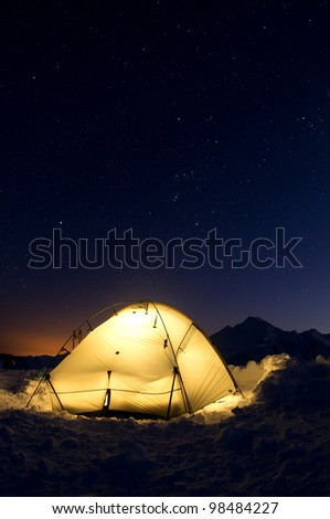 A lit up tent under the twilight stars - stock photo