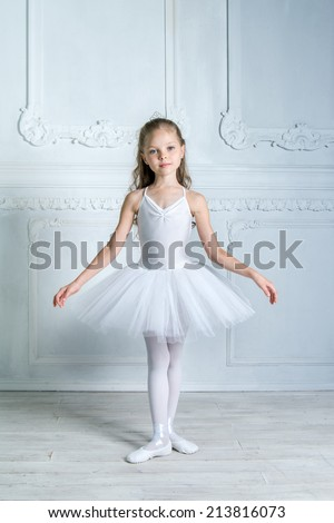 A little adorable young ballerina in a white tutu and pointe is  posing on camera in the interior studio. Little Princess. - stock photo