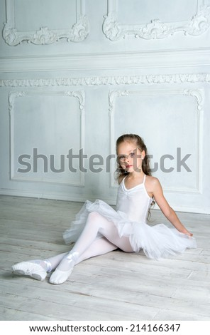 A little adorable young ballerina in white ballet dress tutu is sitting on floor in the interior studio  - stock photo