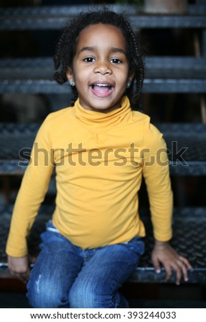 A little African American girl sitting on the stairs. - stock photo