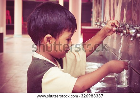a little asian boy press the drinking water,vintage tone - stock photo