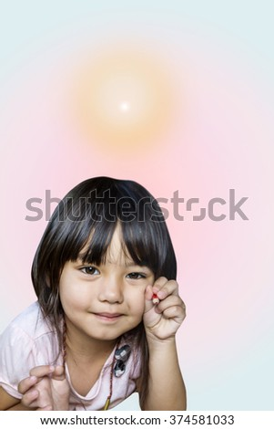 A little asian caucasian girl holding pencil color with soft smiling on her face with bright flare over head shows a brilliant idea - stock photo