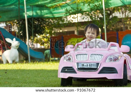 A little baby girl in Car Toy pink color - stock photo