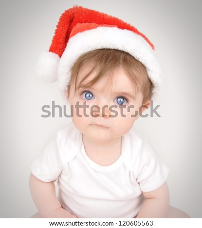 A little baby is sitting down and looking into the camera with big blue eyes and a santa christmas hat on. - stock photo