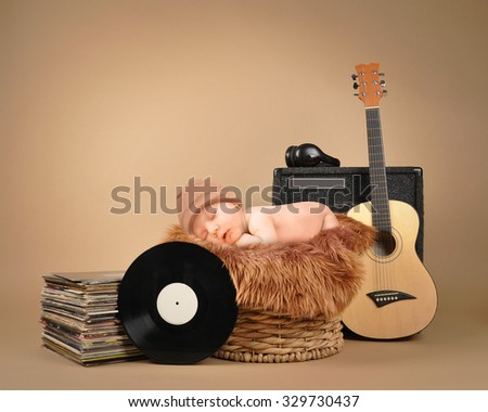 A little baby is sleeping in a basket with music headphones and retro vinyl records on an isolated tan background for a party or entertainment concept. - stock photo