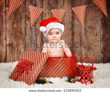 A little baby is wearing a red christmas santa hat and sitting in a present with a wood backdrop for a season or portrait concept. - stock photo