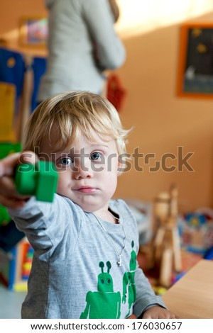 A little blond boy in a play room handing a green block to someone. - stock photo