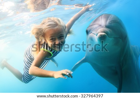 A little blonde seven year old girl diving with funny dolphins underwater. An ocean life sports extreme design. Kid with marine animal. Red sea diving in blue water. - stock photo