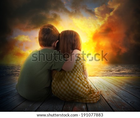 A little boy and girl are hugging and watching the sunset in the sky. The children are sitting on wood for a family, love or vacation concept. - stock photo