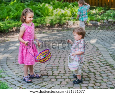 A little boy and girl holding baskets take a break on an Easter egg hunt during the spring season.  A boy in the background holding a basket searches for eggs in a beautiful garden setting.  - stock photo