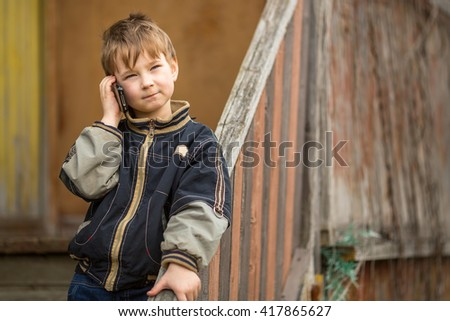 A little boy calls on the phone while standing outdoors. - stock photo