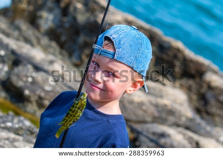 A little boy caught a fish on a fishing rod and slyly look at the camera. Family composition - stock photo