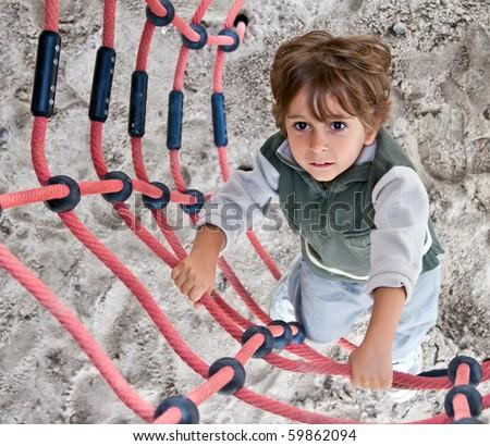 A little boy climbs up the ladder. - stock photo