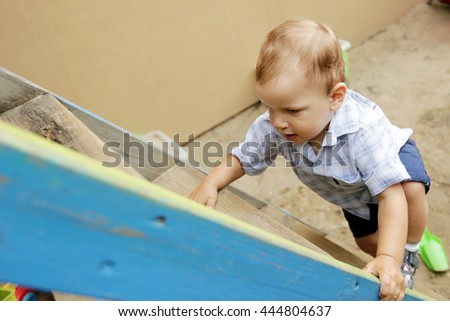 A little boy coming down the wooden stairs  - stock photo