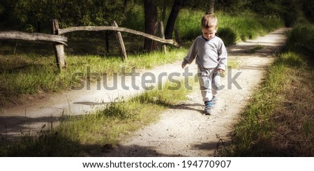A little boy counts steps on a country road - stock photo