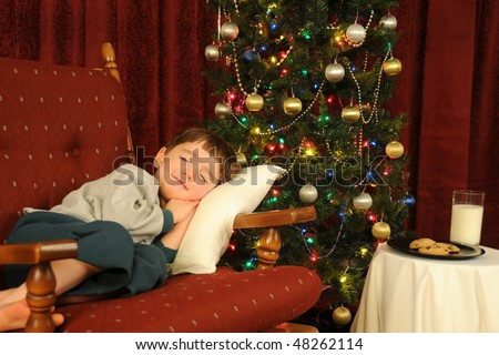 A little boy falls asleep while waiting for Santa on Christmas Eve - stock photo