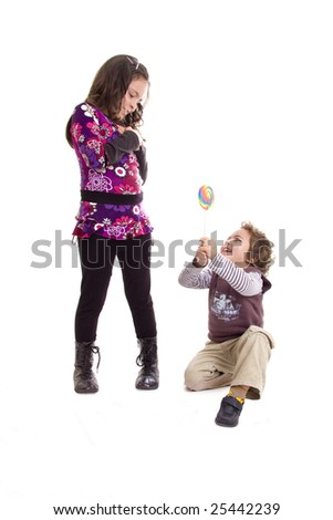 A little boy giving a candy to a little girl on a white background - stock photo