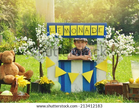 A little boy has an outdoor  homemade lemonade stand with a sign and he looks happy for a small business or money concept. - stock photo