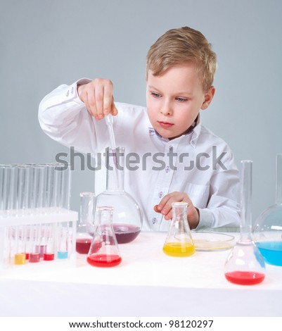 A little boy injuring liquid into a flask and looking at it - stock photo