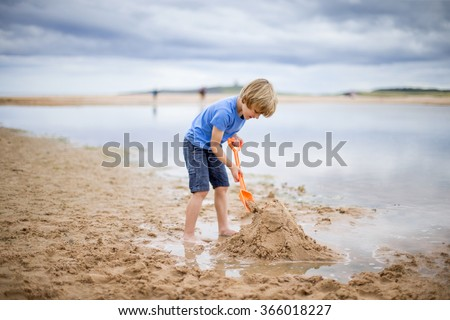 A little boy is at the beach building a sand castle. - stock photo