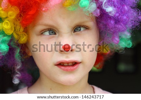 A little boy is making a funny face with crossed eyes while dressed up in a clown costume - stock photo
