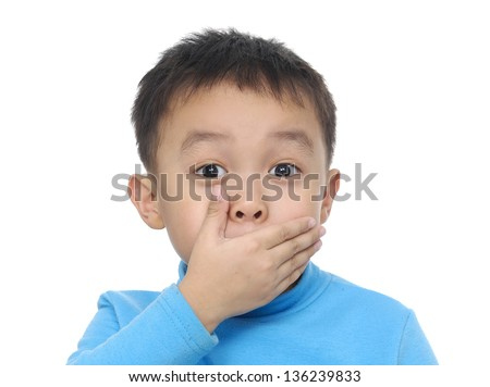 A little boy keeping silence by covering his mouth by hand - stock photo