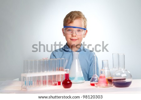 A little boy looking at camera with many flasks near by - stock photo